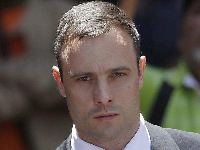 In this file photo, Oscar Pistorius is escorted by police officers as he leaves the high court in Pretoria, South Africa. Pistorius is to be released from jail on October 20.