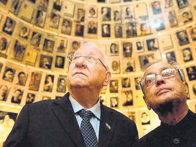 President Pranab Mukherjee looks at pictures of those killed during the Holocaust in the Hall of Names in Jerusalem on Tuesday.