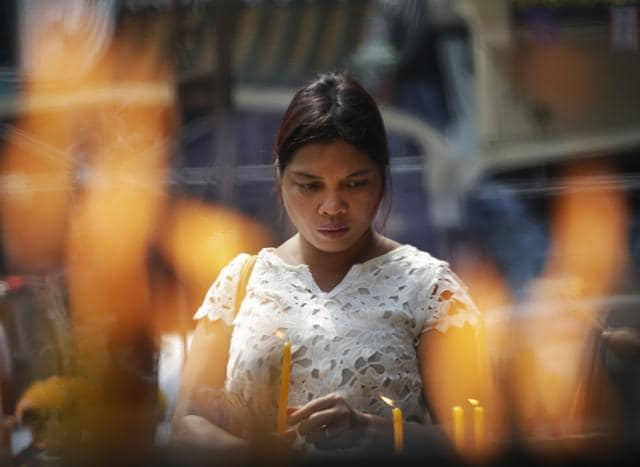 A Thai woman holds incense sticks and candles during prayer at Thian Fah Chinese temple in Bangkok, Thailand.