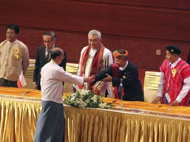 Myanmar President Thein Sein shakes hand with a leader of armed ethnic organisation during the signing ceremony of 'Nationwide Ceasefire Agreement' at Myanmar International Convention Centre, in Naypyitaw, Myanmar. The government and eight smaller ethnic rebel armies signed the ceasefire agreement to end more than six decades of fighting.