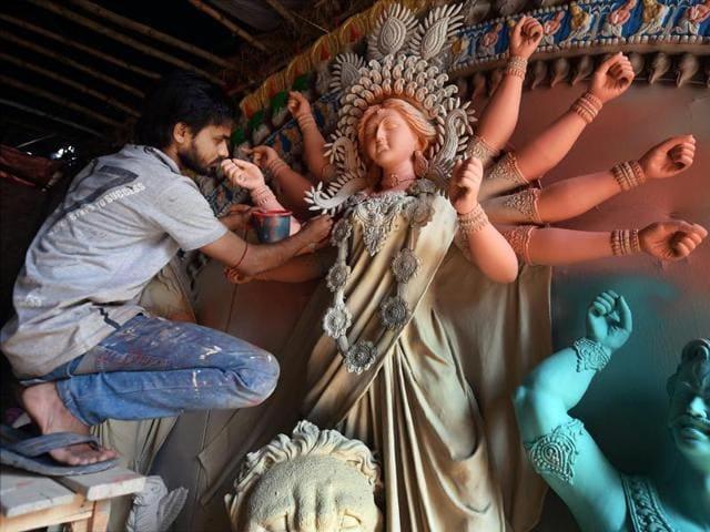 An artisan works on a clay idol of Goddess Durga ahead of Durga Puja.