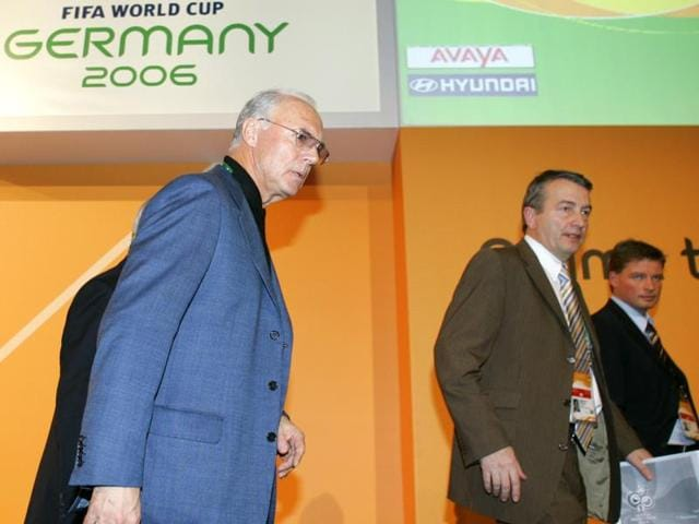 In this file photo, German football legend Franz Beckenbauer (L), the president of the 2006 World Cup organising committee, walks from the stage with Jens Grittner (R), the press spokesperson for the organising committee, and Wolfgang Niersbach, a organising committee member, following a press conference in Leipzig, Germany.