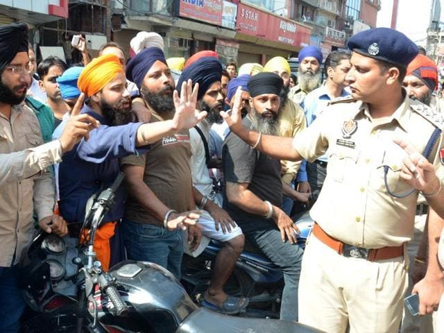 Protesters arguing with a policeman while trying to force a shutdown in Amritsar on Thursday.