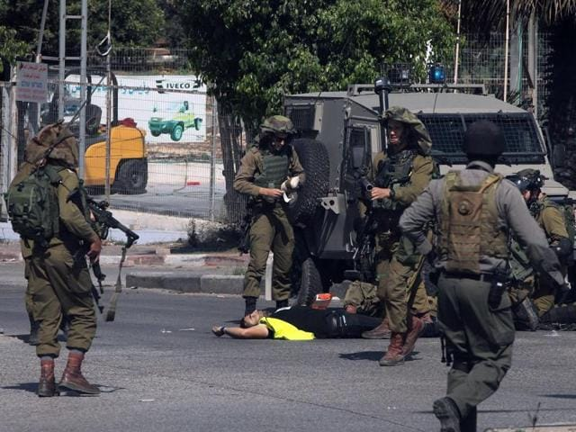 Israeli security forces stand next to the body of a Palestinian man who carried out a stabbing attack against an Israeli soldier on the entrance to the city of Hebron in the occupied West Bank.