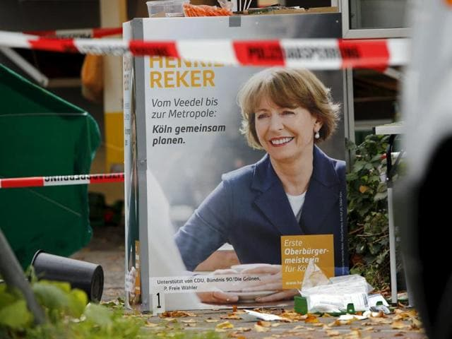 First aid equipment lies on the ground next to an election campaign poster of Henriette Reker in Cologne, Germany.