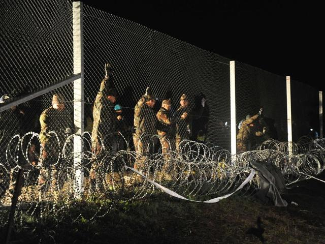 Hungarian police and soldiers close the border between Hungary and Croatia with barbed wire and a fence in Botovo.