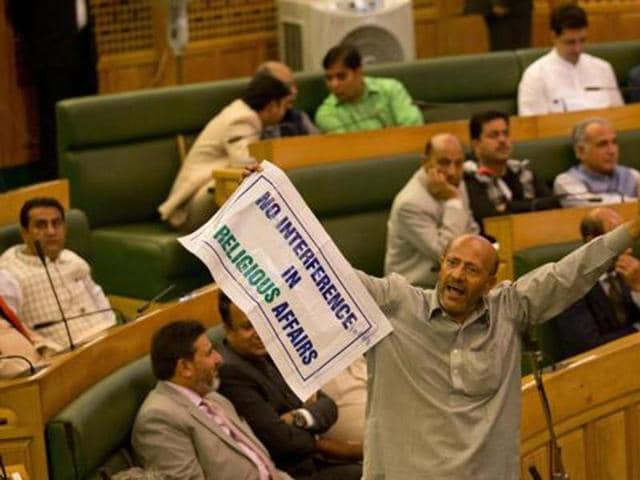 Engineer Rashid, an independent legislator, holds a banner as he disrupts the first day of Jammu and Kashmir state's autumn assembly session in Srinagar.