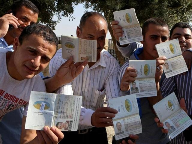 Egyptians who live in Jordan pose for a photo with their passports after voting in the country's first parliamentary election since the 2013 military overthrow of Islamist President Mohammed Morsi at the Egyptian embassy.