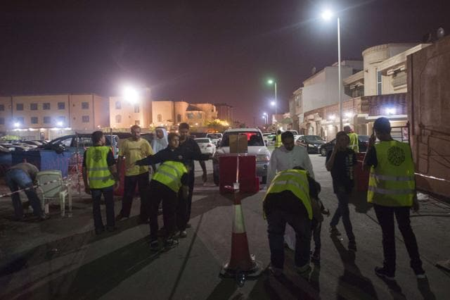Saudi Shia worshipers are frisked by members of security as they make their way to a hussainiya, a Shia hall used for commemorations in Qatif.