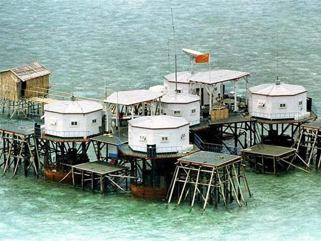 A Chinese flag and a satellite dish are prominently displayed in a structure built by China in one of the islands in the Spratlys in  the South China Sea.