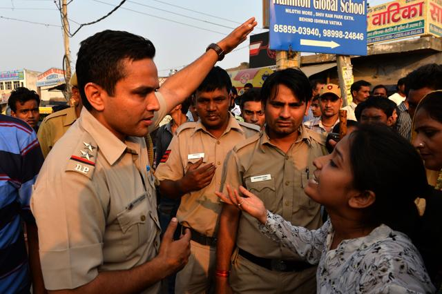 A woman shouts at a police personnel during a protest near the home of a minor girl who was raped in New Delhi on October 17.
