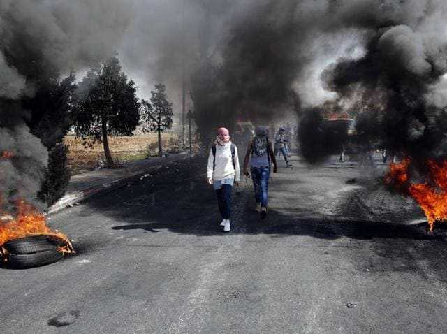Palestinian protesters walk between burning tires during clashes with Israeli security forces near the Beit El settlement on the outskirts of Ramallah.