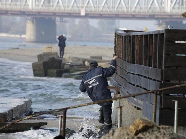 Ukrainian police officers investigate the coast near to where the boat Ivolga capsized on Saturday,  in a storm near the major port city of Odessa, Ukraine, Sunday, Oct 18. The Ukrainian emergency services have blamed the accident on the overloading of the vessel, which was carrying 37 people, more than twice the maximum allowed of 15.