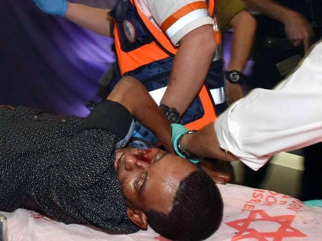 A wounded Eritrean man who later died of his wounds, is evacuated at the main bus station in the southern Israeli city of Beersheva on October 18, 2015, after he was mistakenly shot by an Israeli security guard and beaten by a mob during an attack.