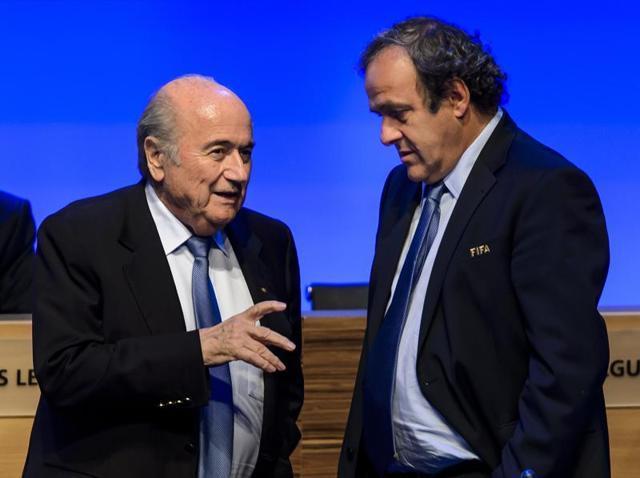 A June 11, 2014 file photo of suspended Fifa president Sepp Blatter, left, talking to suspended Uefa president Michel Platini.