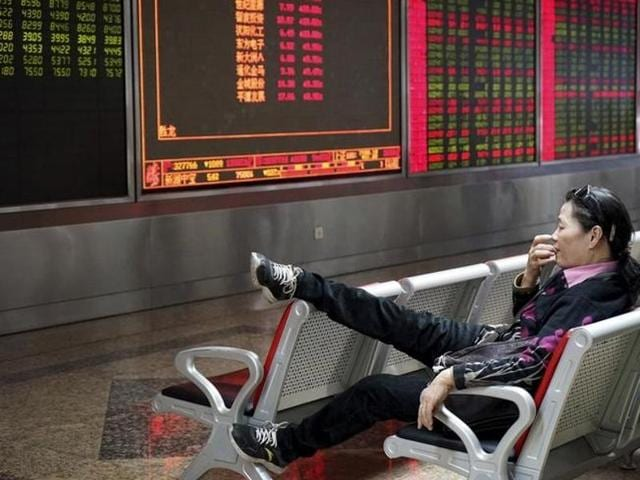 An investor rests on a chair in front of an electronic board showing stock information at a brokerage house in Beijing.