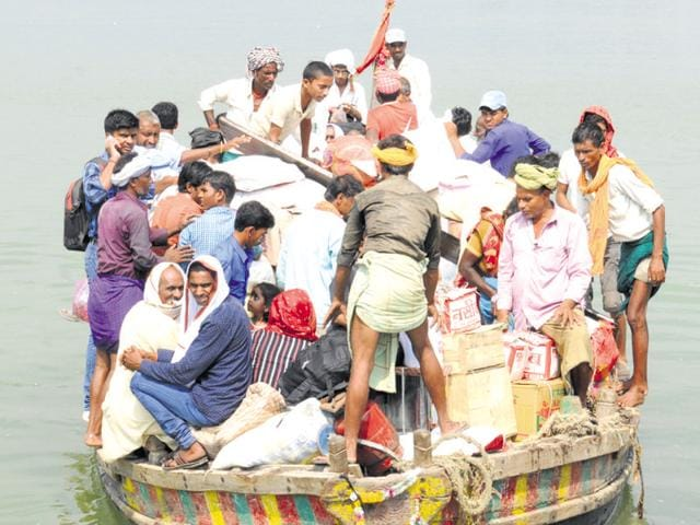 In the absence of a concrete bridge, the people of Raghopur diara are forced to use boats to reach the mainland. (AP Dube/HT Photo)
