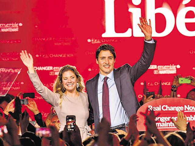 Canadian Liberal Party leader Justin Trudeau and his wife Sophie wave on stage in Montreal on October 20, 2015 after winning the general elections.