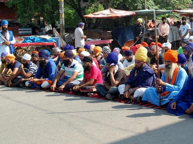 Sikh protestors sitting on a road outside the bus stand in Kapurthala on Tuesday.