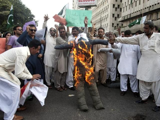 People burn an effigy of Indian Prime Minister Narendra Modi to protest against the Shiv Sena in Karachi.