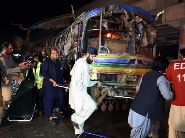 Pakistani volunteers and residents move the body of a blast victim from a bus after a bomb explosion in Quetta on October 19, 2015.