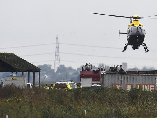 A police helicopter hovers over the site of the crash.
