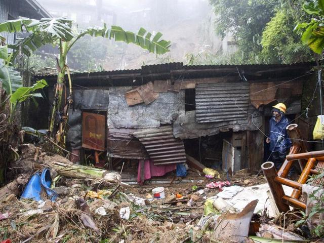 A worker inspects a wrecked house that was hit by a landslide in Baguio City, north of Manila.