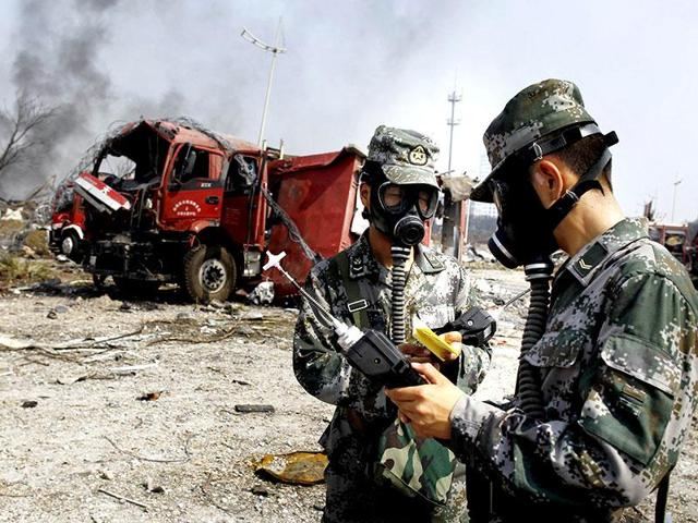 Soldiers of the People's Liberation Army anti-chemical warfare corps work next to a damaged firefighting vehicle at the site of an earlier explosion in Tianjin (Reuters photo)