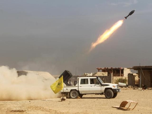 Iraqi Shiite fighters from the Popular Mobilisation units, fighting alongside Iraqi government forces, fire a rocket during a military operation against Islamic State (IS) group jihadists as they advance towards the centre of Baiji.