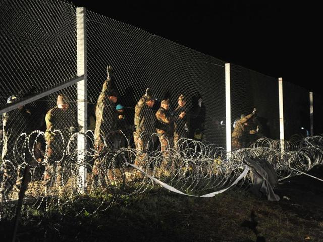 A group of migrants, seen through razor wire, crosses a border from Croatia near the village of Zakany, Hungary.  Hungary's construction of a razor-wire fence along its border with its EU neighbour is the latest sign that the union is unravelling.