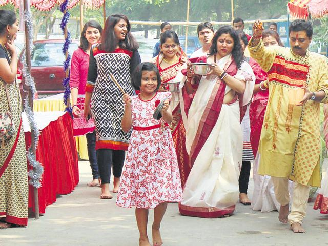 Residents take part in puja celebrations at Greenwood City A-block on Wednesday.