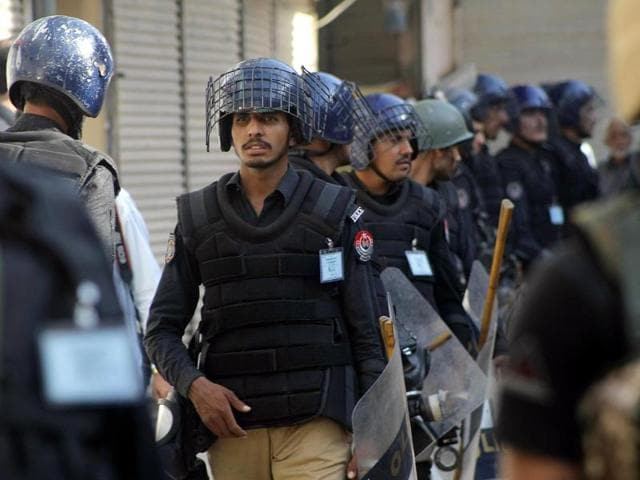Pakistani police officers guard a Shiite procession during Muharram in Peshawar, Pakistan, on Thursday. A government official said a powerful bomb at a Shiite mosque in southwest Pakistan killed many.
