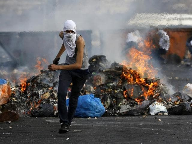 A Palestinian protester clashes with Israeli security forces (unseen) in the West Bank town of Al-Bireh.