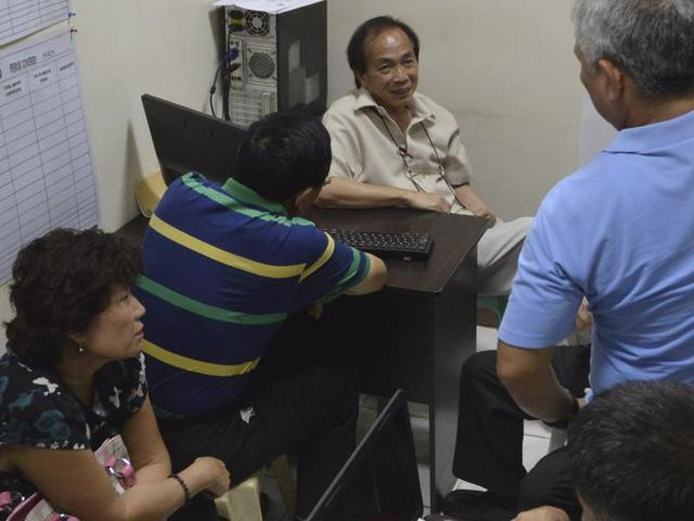 Li Qingliang (2nd from left), the suspect in a shooting of three Chinese diplomats, sits near his wife Guo Jing as he is questioned by police in Cebu city, central Philippines.