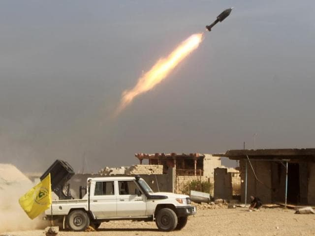 Iraqi Shiite fighters from the Popular Mobilisation units, fighting alongside Iraqi forces, fire a rocket during a military operation against Islamic State.