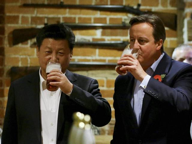 Britain's Prime Minister David Cameron,  drinks beer with Chinese President Xi Jinping.