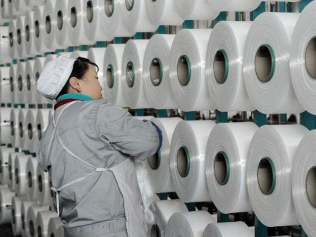 This picture shows a Chinese worker checking a machine making blankets for exports at a factory.