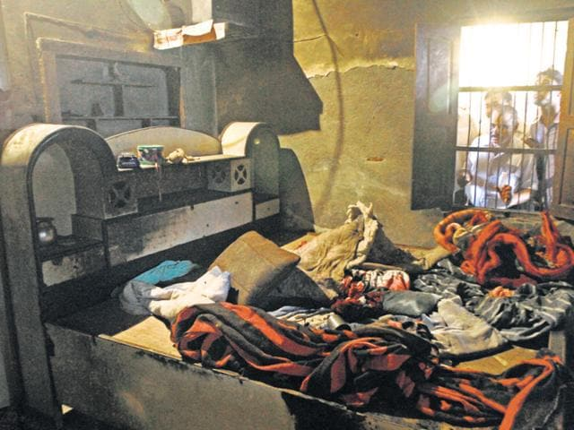 Curious onlookers peep through the window into the room in which two kids were burnt alive in Sunperh, Ballabgarh.