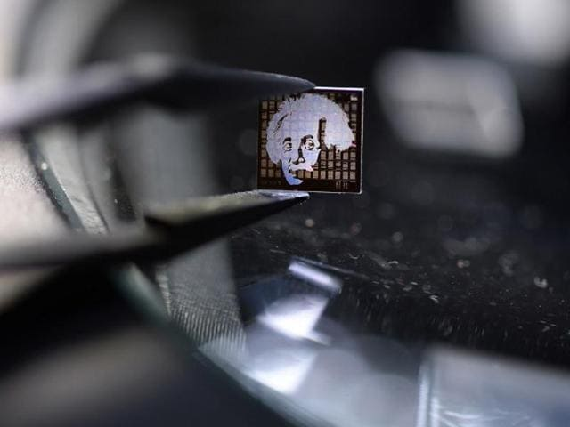 A nanochip made of quartz glass with a picture of Albert Einstein under a microscope of technology company NanoJewellery