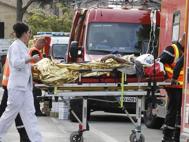 Rescue workers carry an injured person on a stretcher near the site where a coach carrying members of an elderly people's club collided with a truck outside Puisseguin near Bordeaux.