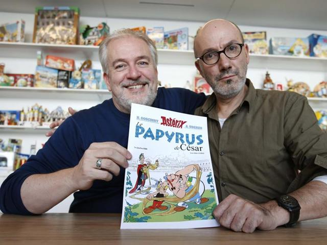Author Jean-Yves Ferri (R) and illustrator Didier Conrad (L) pose with a print of the cover of their new comic book