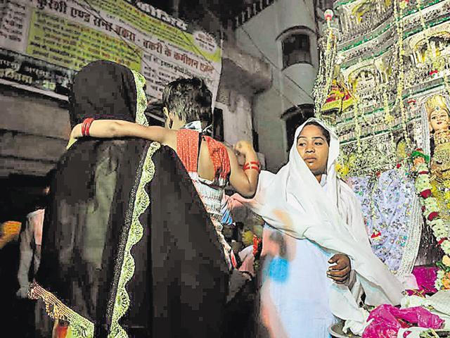 A woman brings her child to pay respect to the Eunuchs' Tazia in Bhopal. The tazia was immersed later in the night.
