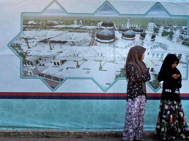 Acehnese girls stand near a banner showing an image of the Baiturrahman Grand Mosque, at dusk in Banda Aceh, Aceh province, Indonesia, Friday, Oct. 23, 2015. A law that makes gay sex punishable by public caning took effect Friday in the conservative Indonesian province. Aceh is considered more devout than other areas of Muslim-majority Indonesia and is the only province allowed to observe a version of Islamic Shariah law.