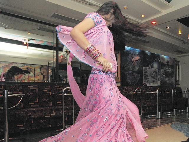 A dancer entertains customers in a bar at Andheri West.