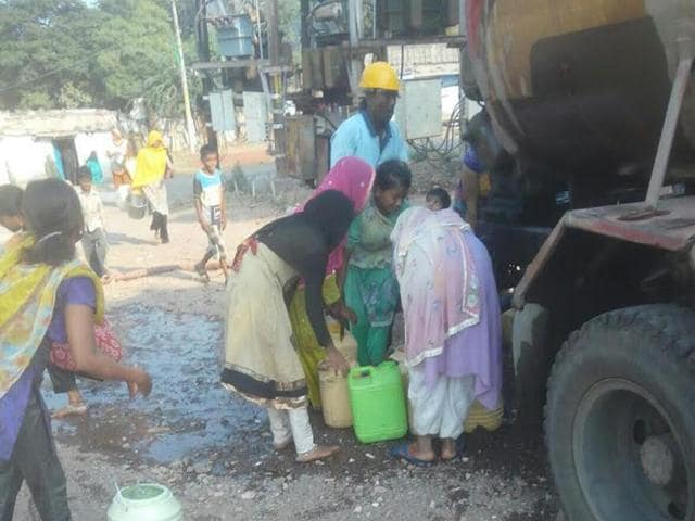 Residents collect water during the relaxation in curfew in Khargone.