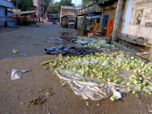 A woman collecting potatoes from Sabzi Mandi in Khargone on Sunday during relaxation of curfew.
