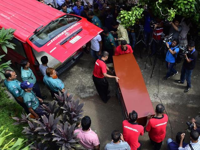 This photo taken on October 14, 2015 shows workers carrying the coffin containing Italian citizen Cesare Tavella, who was shot to death on September 28 by unidentified assailants, from the morgue at the Dhaka Medical College in Dhaka.