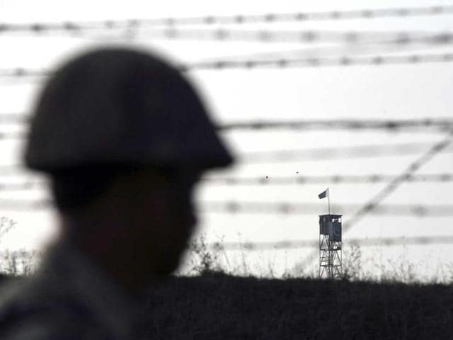 A Border Security Force (BSF) soldier patrols the fenced border with Pakistan against the backdrop of a Pakistani tower in Suchetgarh, southwest of Jammu.