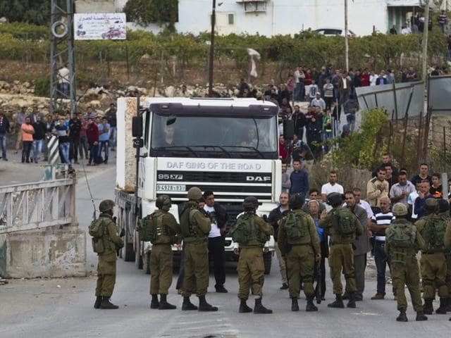 Israeli soldiers secure the area next to the scene of a stabbing attack near the West Bank town of Hebron.