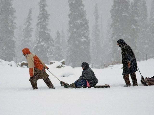 Tourists enjoy sledge ride during the season's first snowfall at famous Ski resort Gulmarg 55 km's from Srinagar on Saturday.